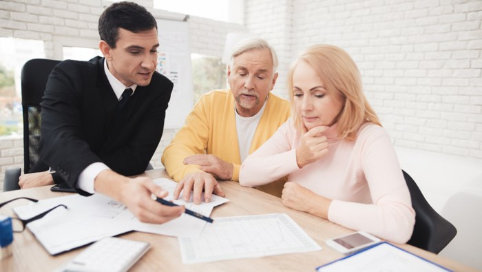 Older couple listening to real estate agent explain what to do to sell their house.
