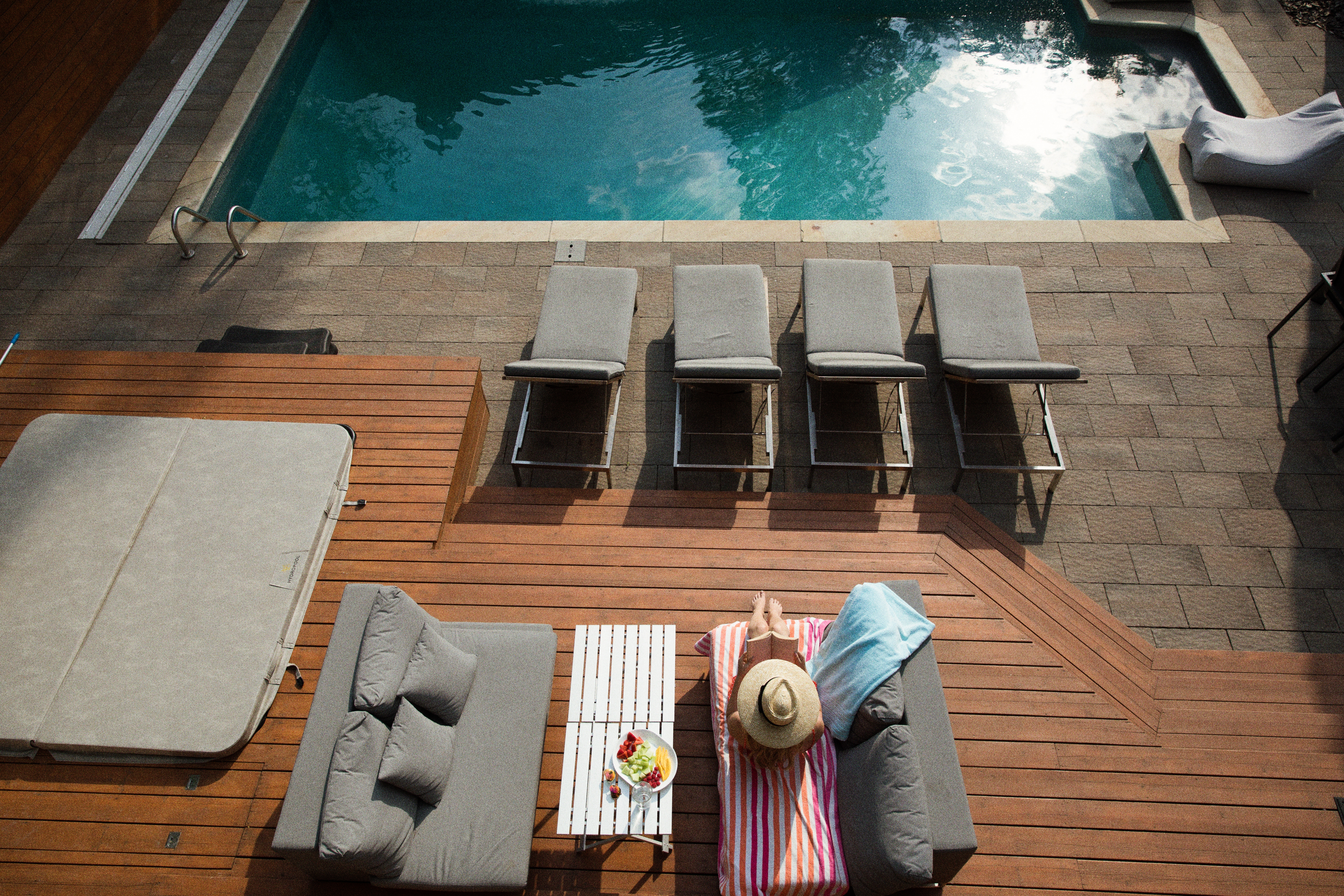 Woman on lounge chair outside house's pool.