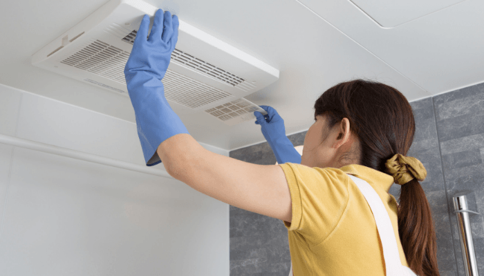 A woman maintaining a home by replacing exhaust fans.