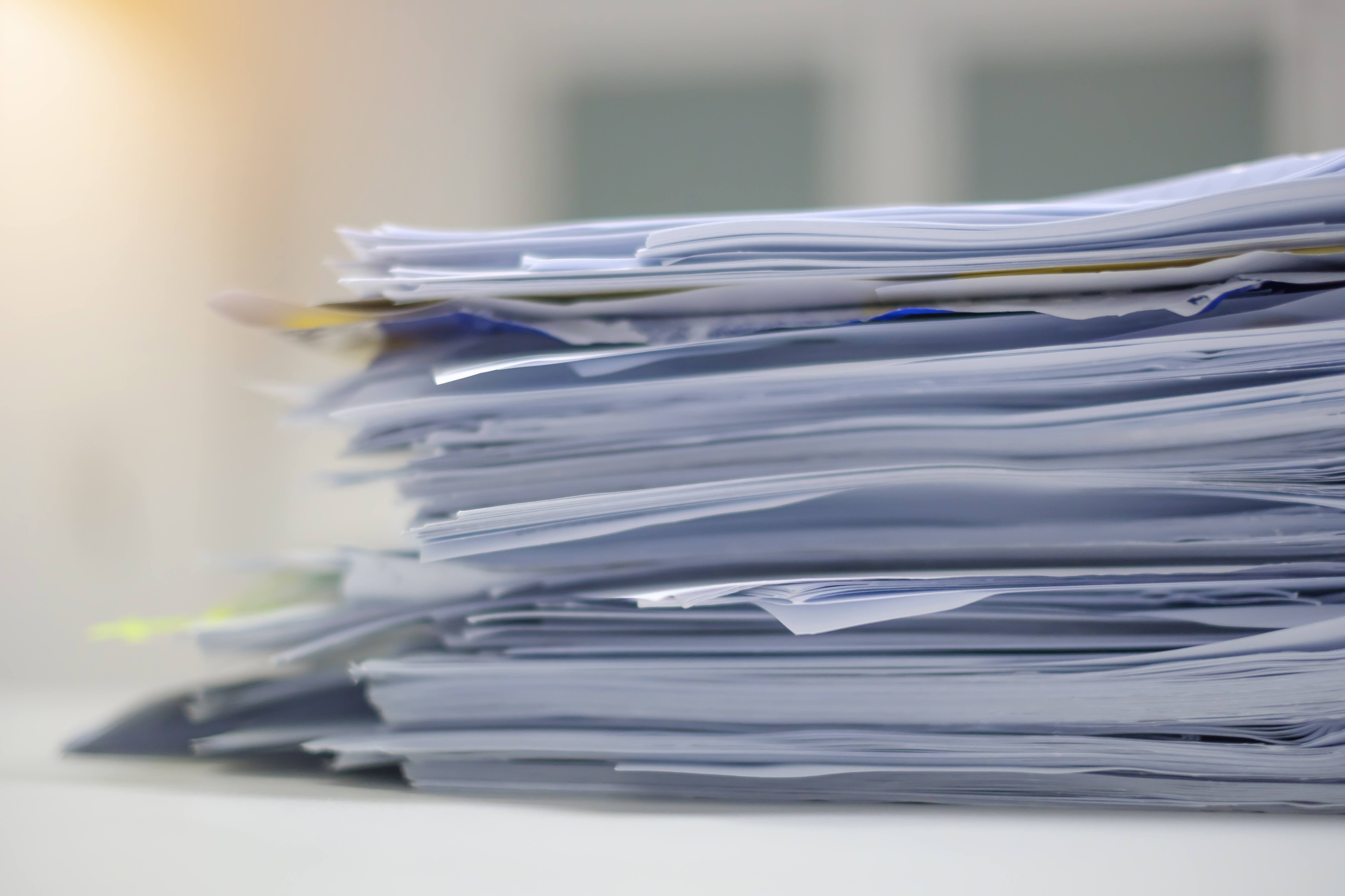 A pile of papers that are stored as home records.