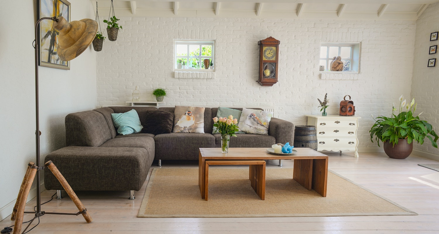 A cozy living room with white brick walls and a brown sofa to symbolize how buying a house is worth it