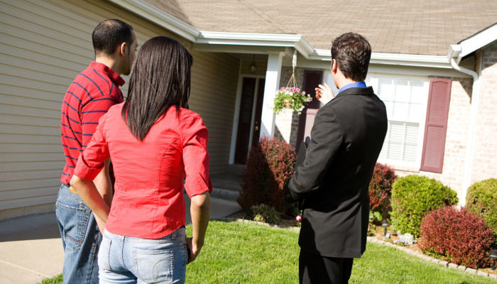 A real estate agent showing buyers around at an open house, which is typically what happens.