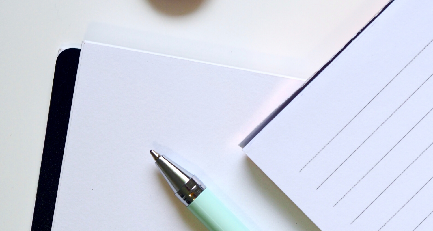 A pen and paper to write questions to ask a real estate agent.