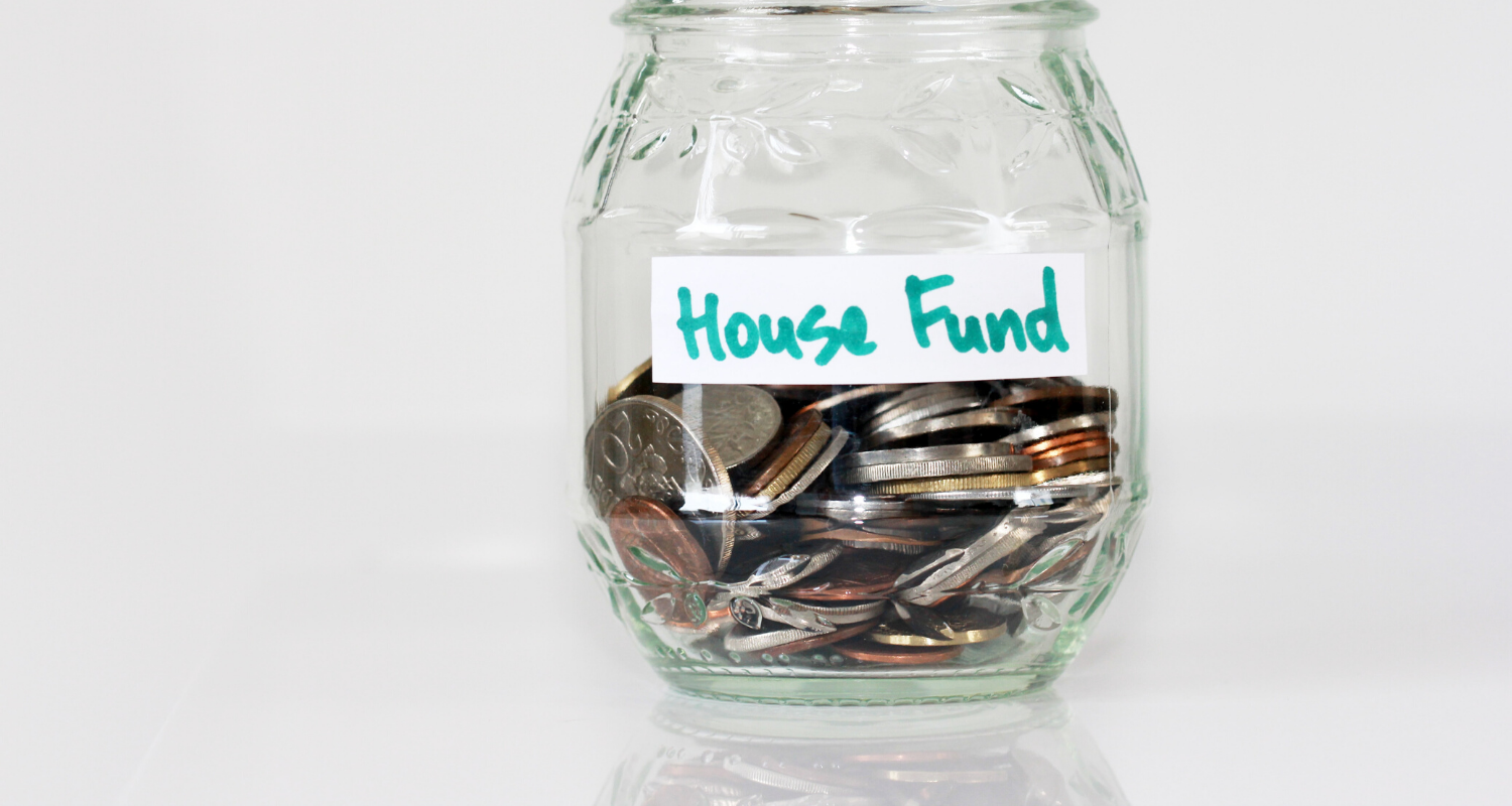 A jar of coins with a label that says house fund.