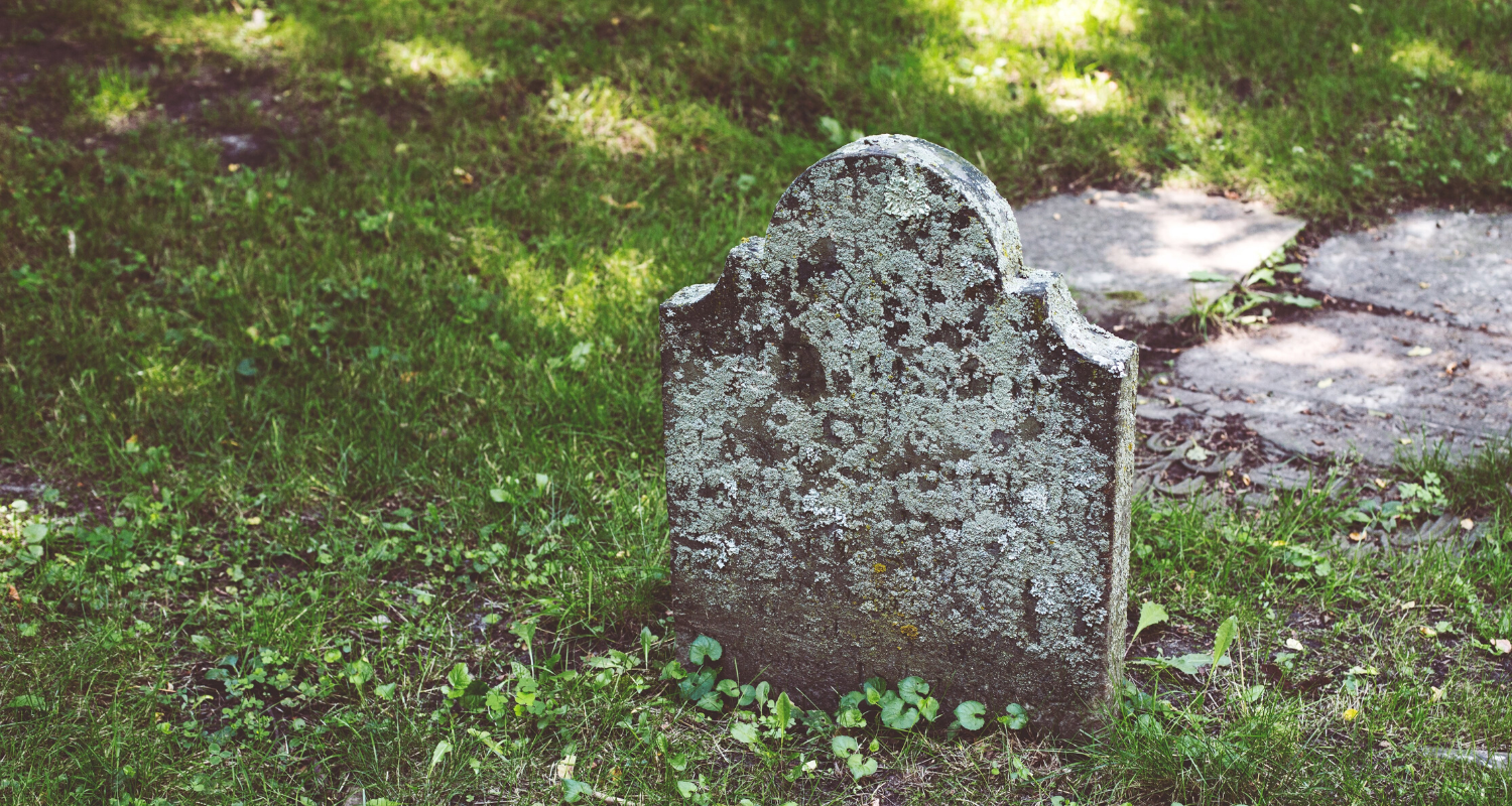 A headstone in a cemetery that you could have property next to.