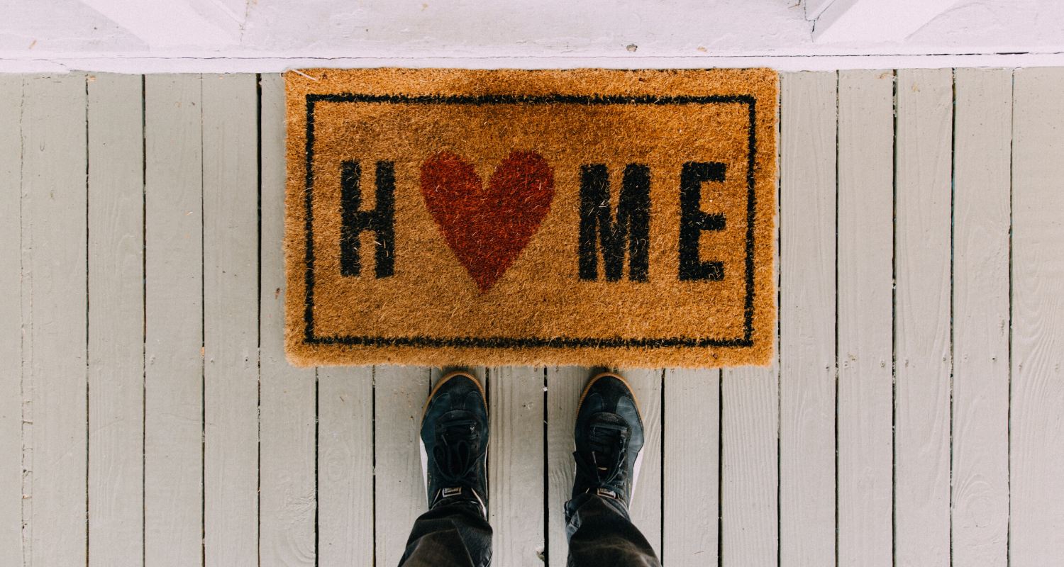 "Feet standing at a welcome mat that says ""Home"" with a heart for the O, on a white porch"