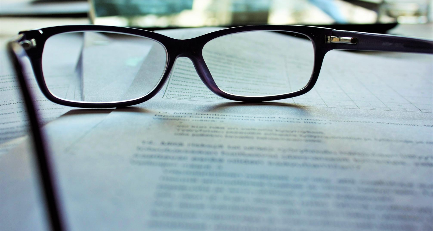 A pair of glasses rest on a contract.
