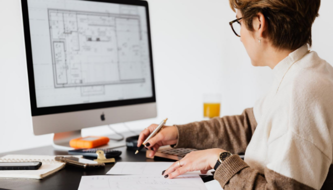 A woman sitting at a computer working on new construction home plans.