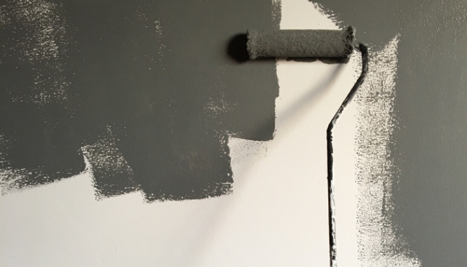 Someone using a paint roller to paint a white wall gray after moving into a new house.