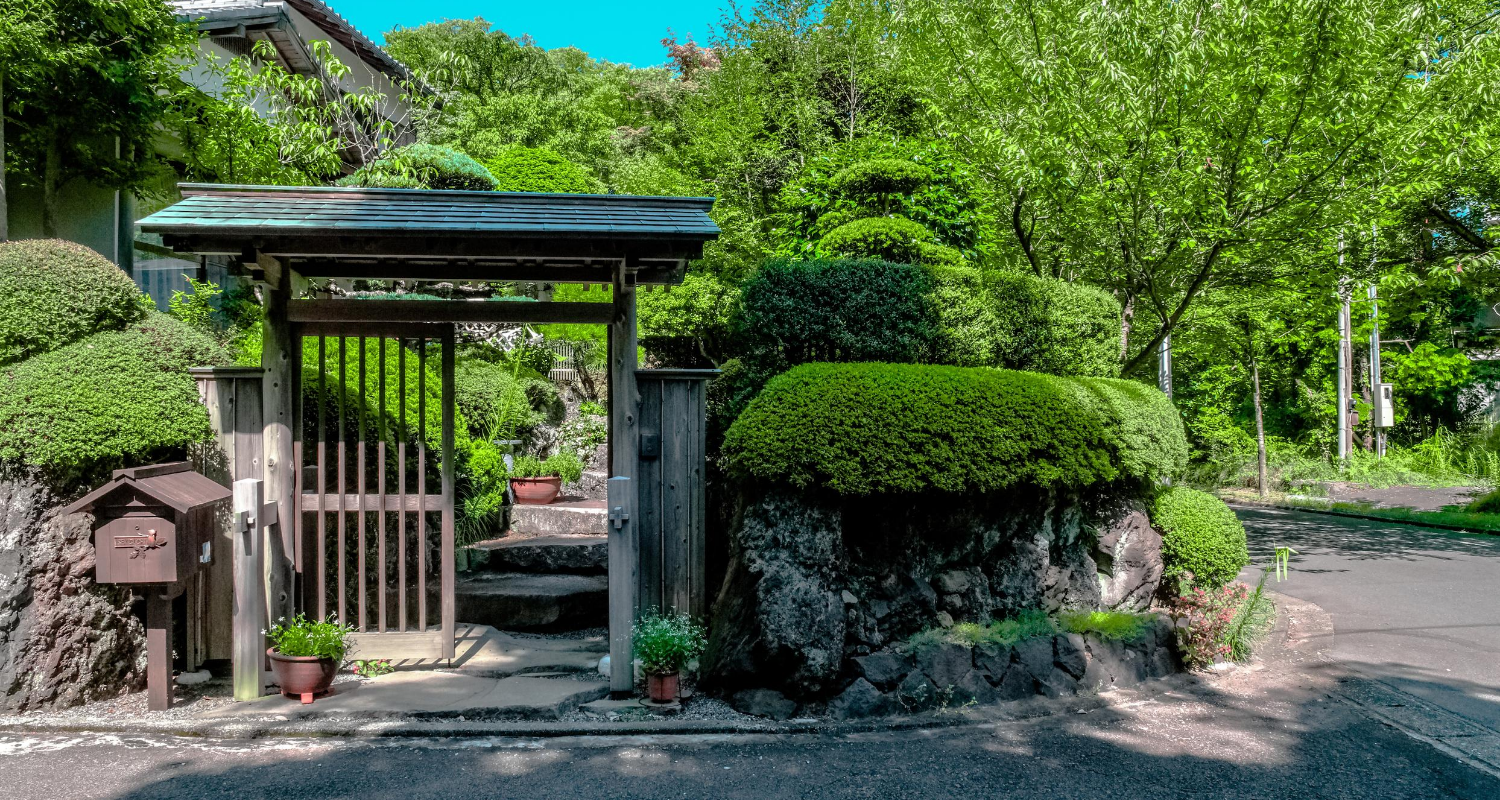 A gate and hedge bushes in front of a home, an upgrade that could increase the value.
