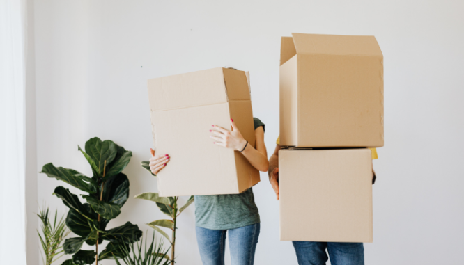 A couple holding moving boxes after selling real estate.
