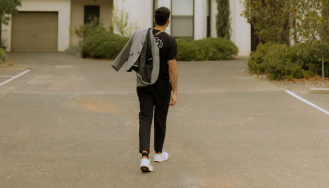A man walking up to an open house.