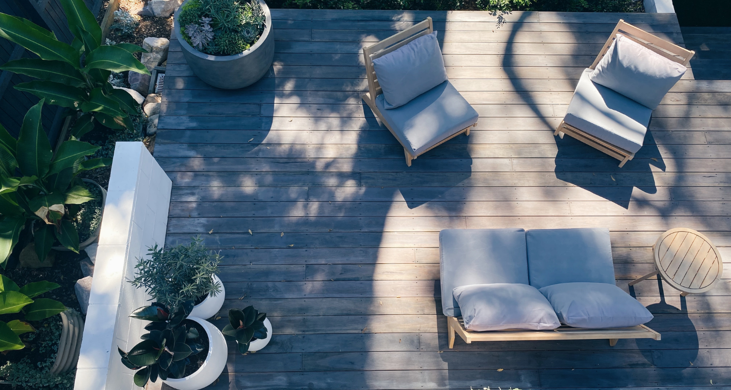An image of a deck with deck furniture to demonstrate how to clean a deck before staining.