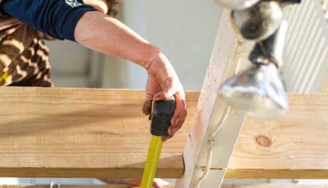 A builder measures the gaps between beams as part of the steps to building a house.