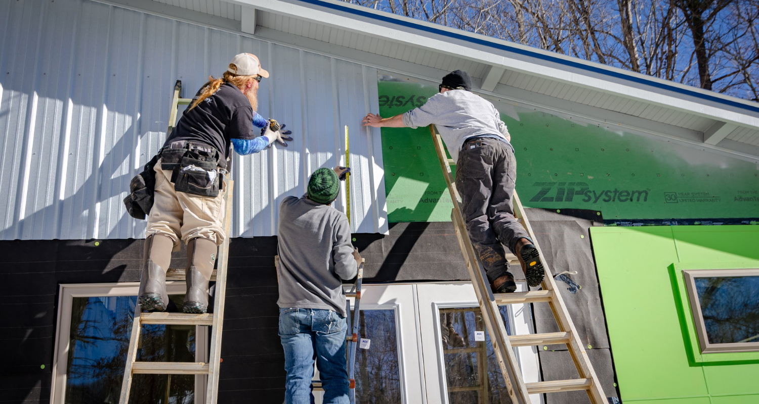Contractors install the siding on a new house, one of the many steps to building a house.