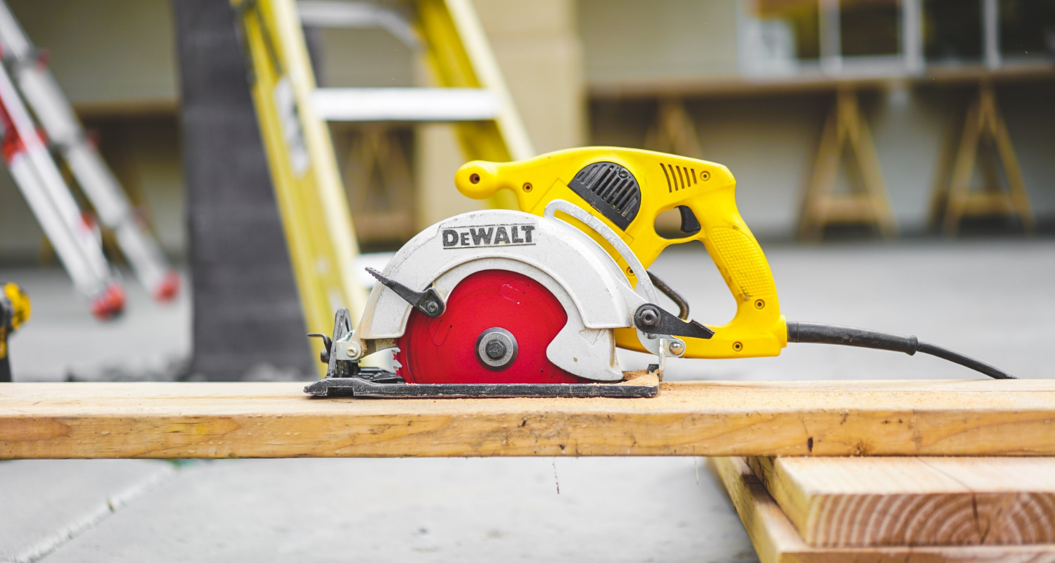 A saw and wooden plank at a home construction site, which can help you decide whether to add on or move.