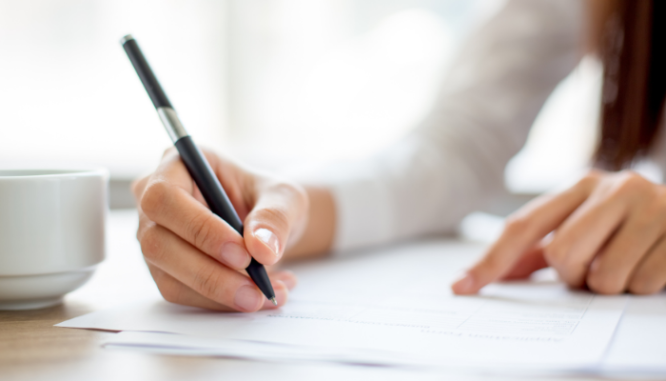 A person signing documents that may have to do with buying a house for cash and reporting to the IRS.