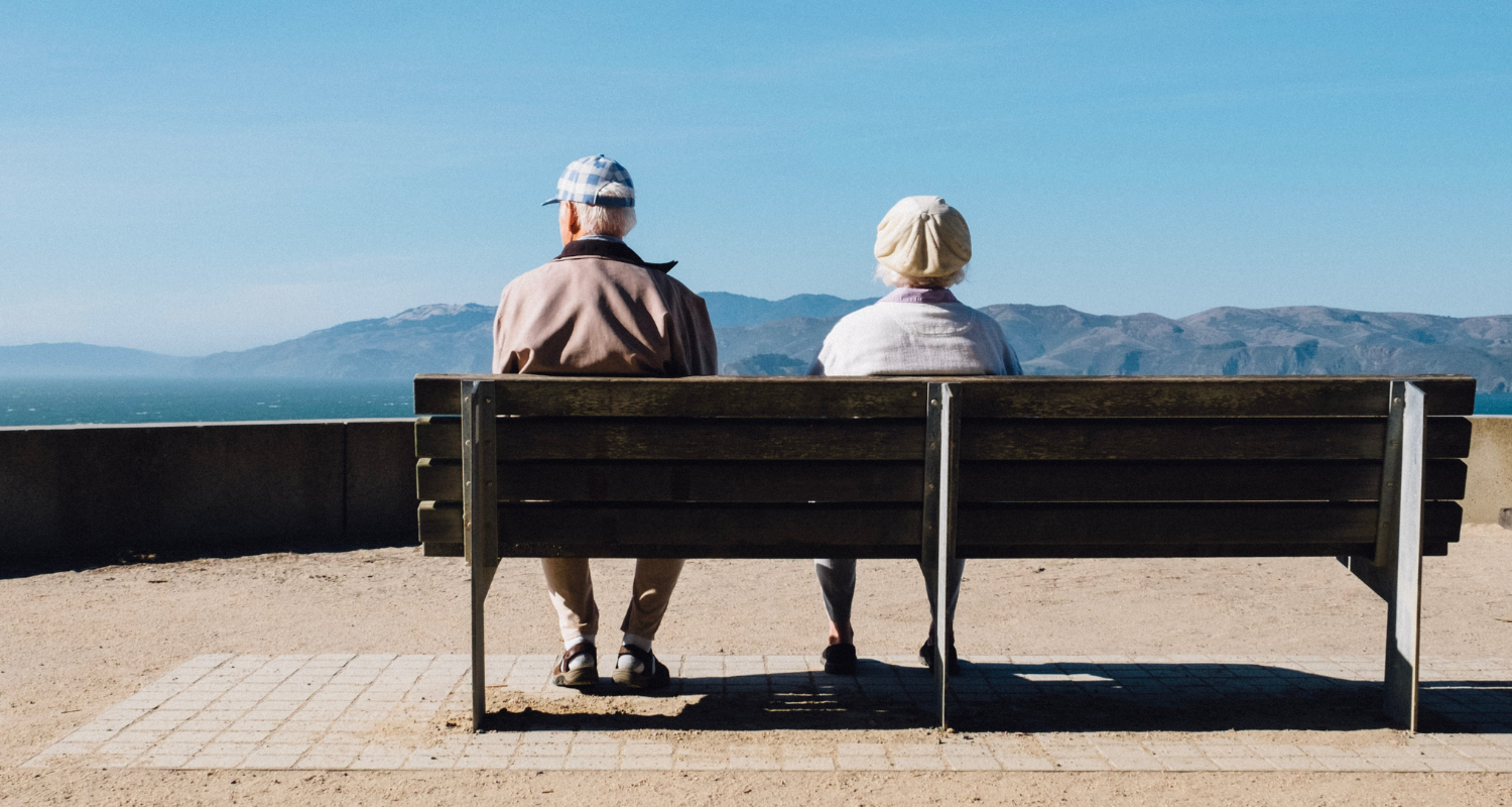 An elderly couple with dementia sitting on a bench near their house.