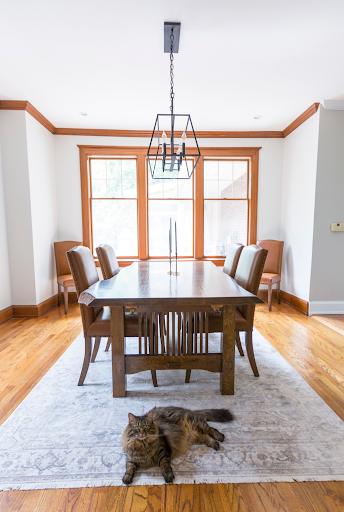 A dining room that has wood trim that has the paint removed.