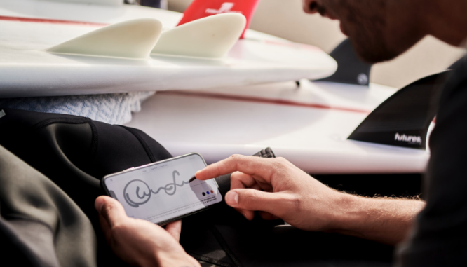 A man signing closing documents on his phone as a buyer.